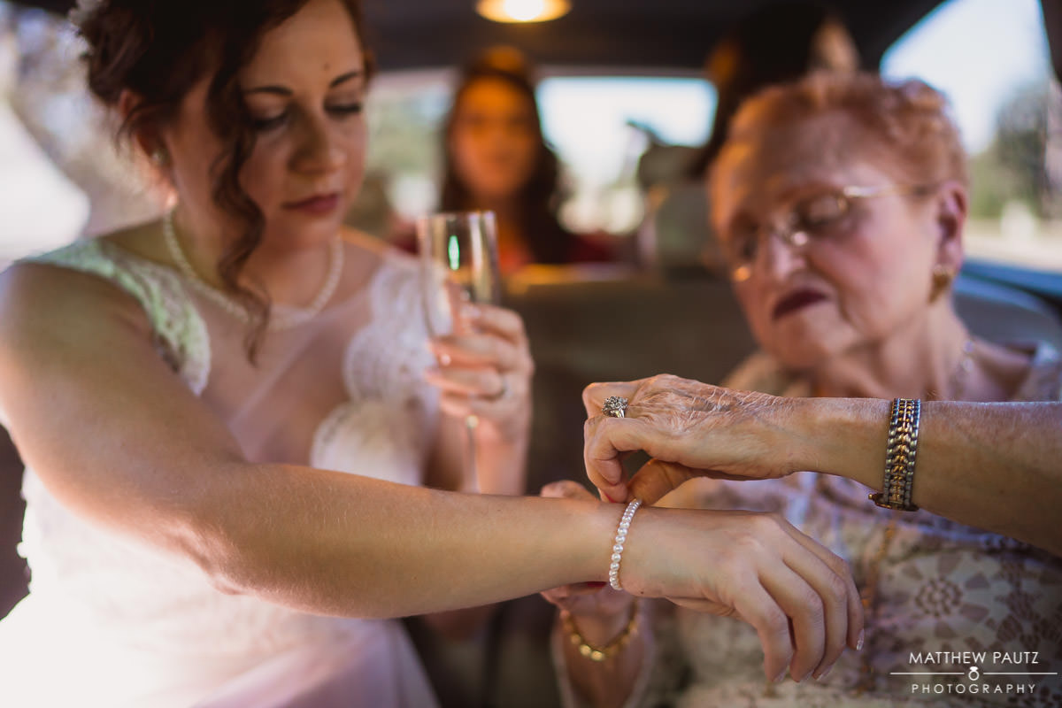 bride's grandmother putting bracelet on bride before wedding ceremony
