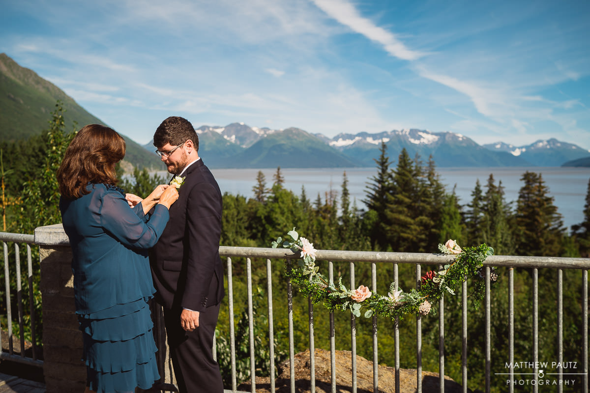 Groom's mother pinning boutonniere before destination wedding ceremony in Alaska