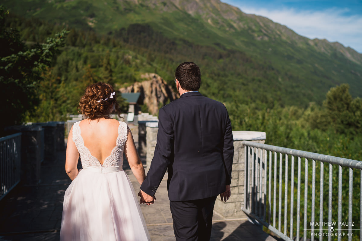 bride and groom walking hand-in-hand away from destination wedding ceremony location