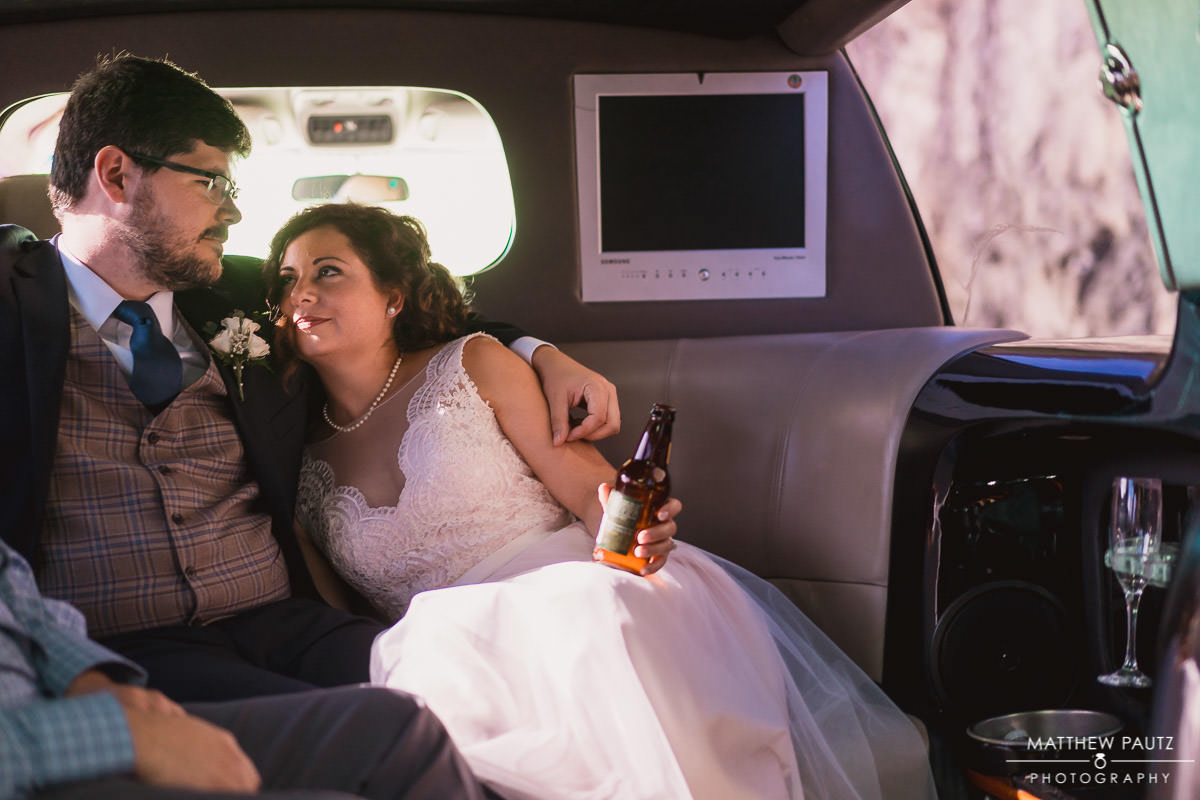 bride and groom riding in a limo after wedding ceremony