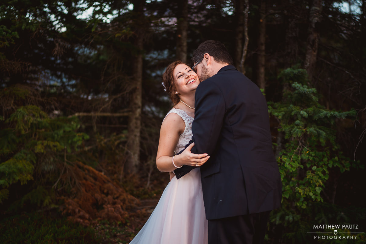 Bride smiling while groom kisses her neck
