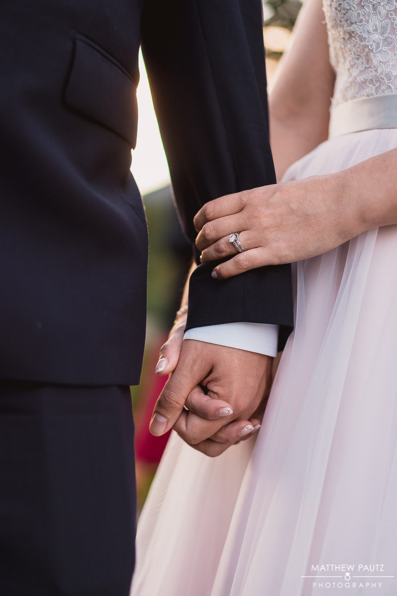 closeup of bride and groom holding hands outside at sunset