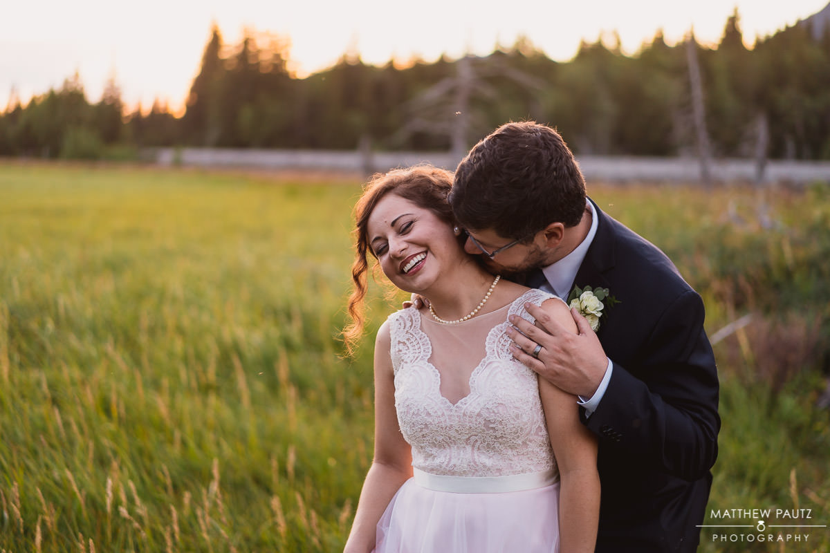 Groom kisses bride's neck at sunset after destination wedding in Anchorage