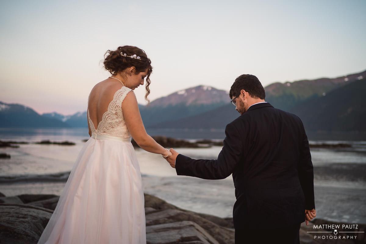 groom helping bride over rocks after anchorage destination wedding