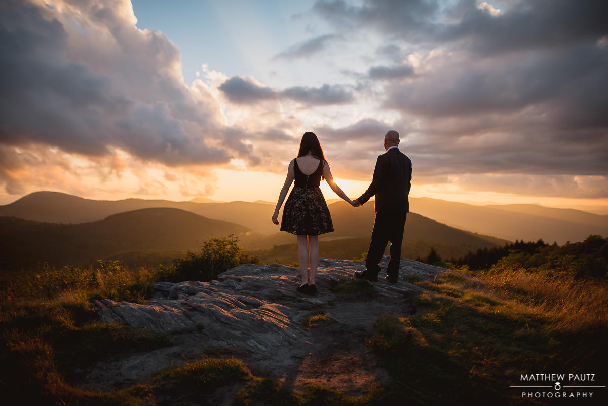 Couple holding hands at sunset on mountaintop