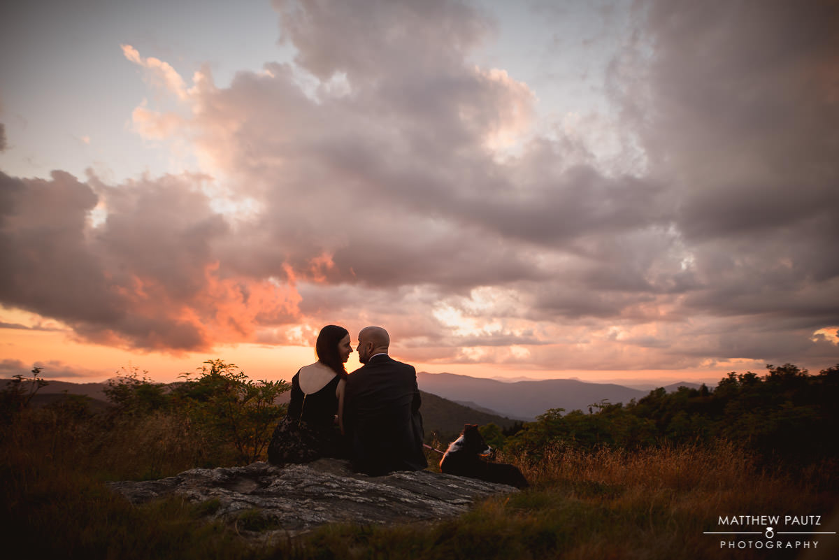 engaged couple sitting and enjoying sunset on a mountaintop