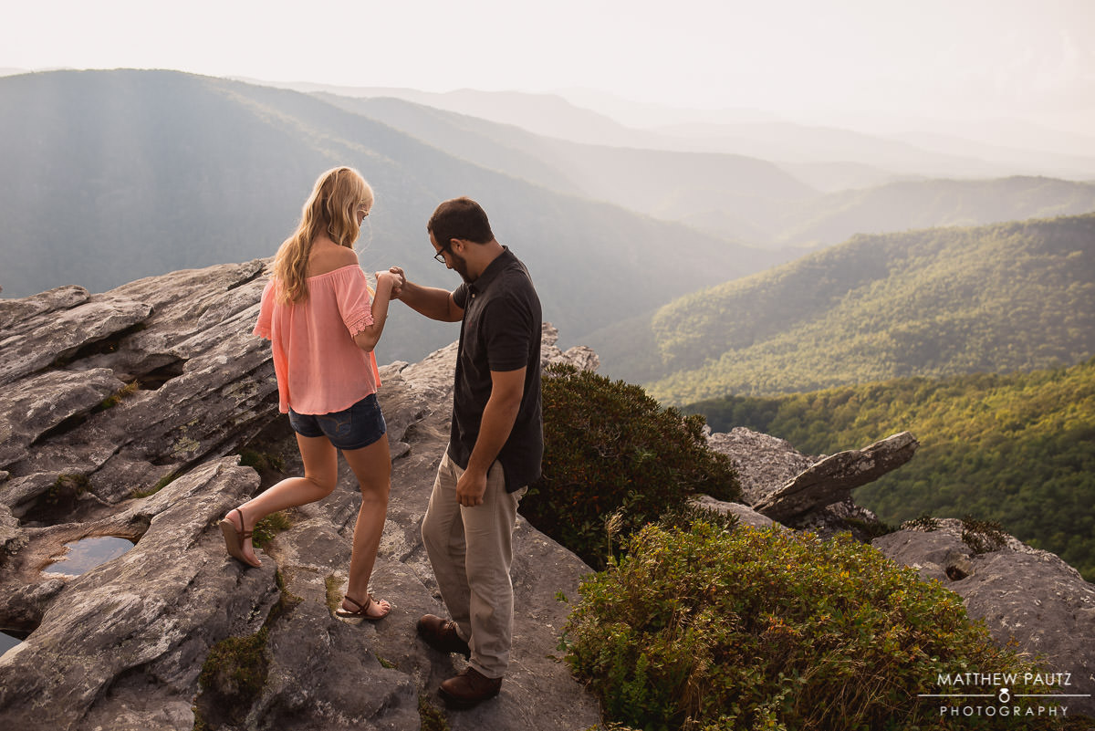 Engaged couple hiking around on a mountaintop