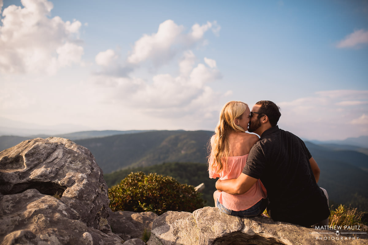Engaged couple kissing on a mountain at sunset