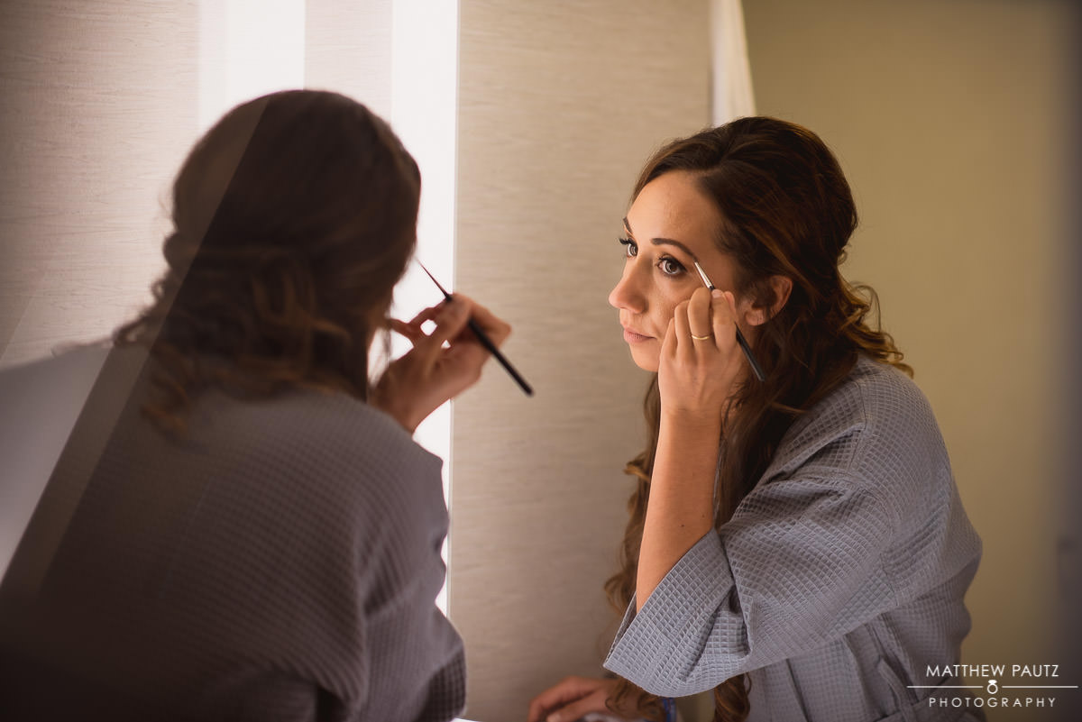 bridesmaid applying makeup before wedding ceremony