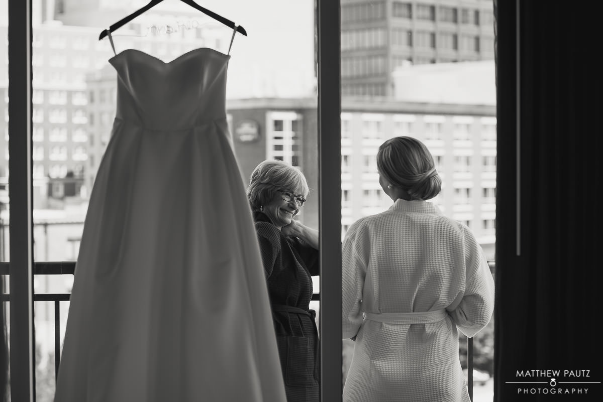 mother of the bride laughing with bride on balcony in front of wedding dress