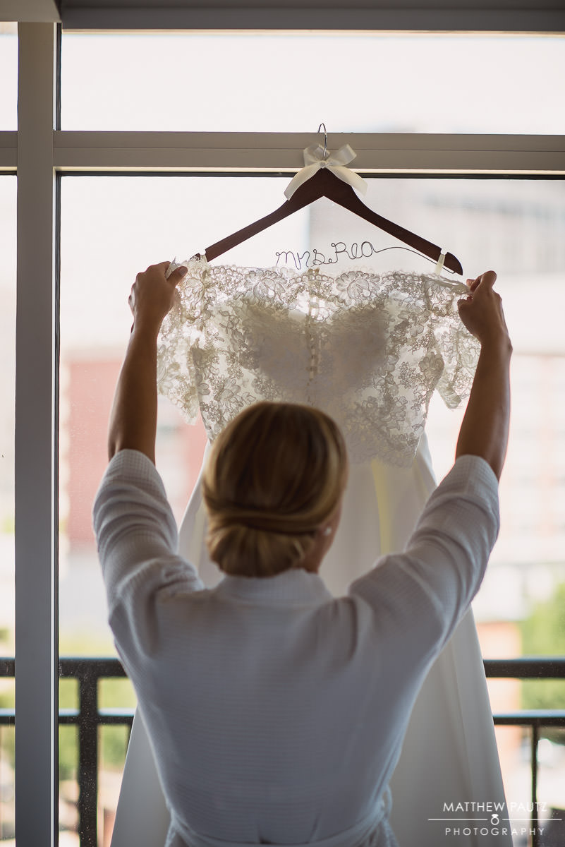 bride hanging up wedding dress before wedding day