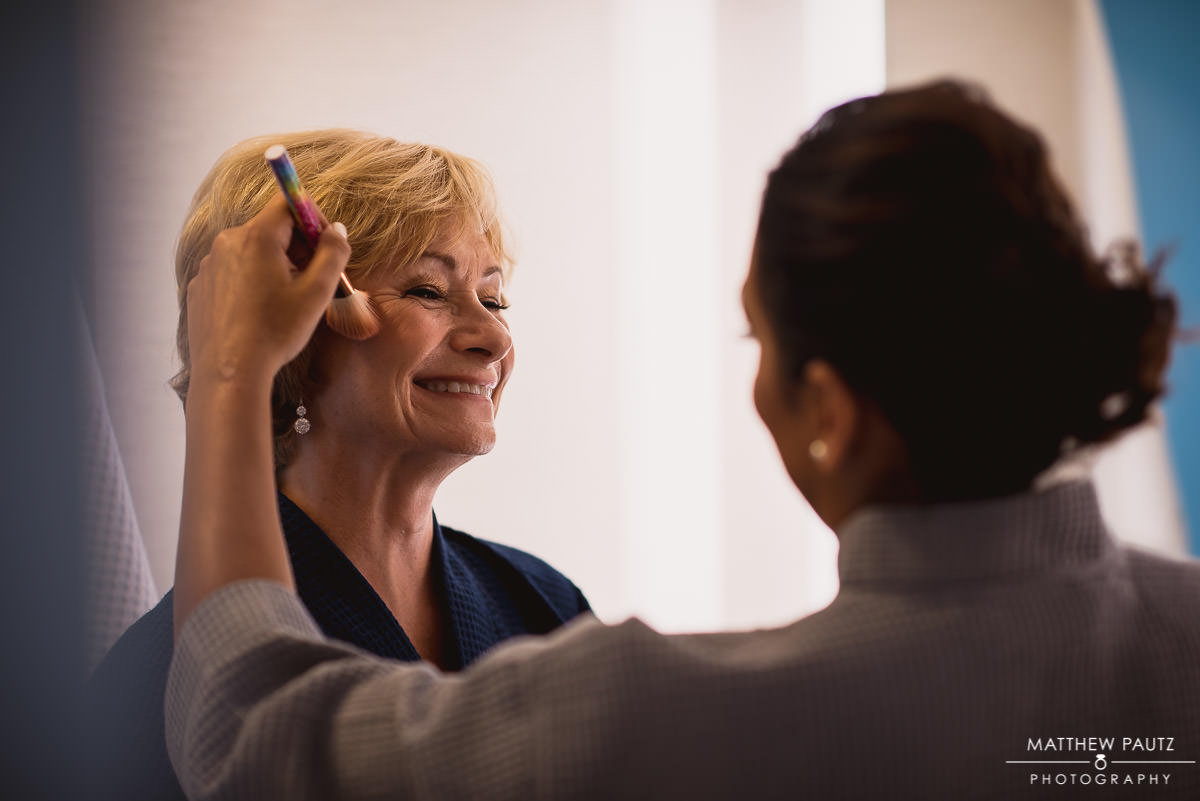 mother of the bride having makeup applied