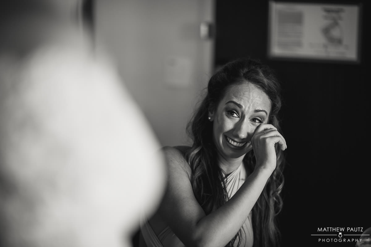 bridesmaid crying after seeing bride in wedding dress