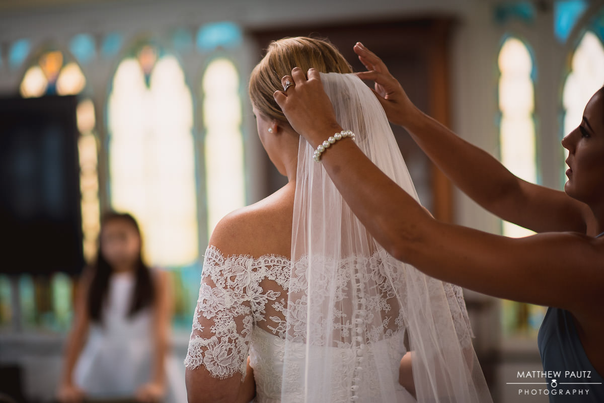bride putting veil on before ceremony