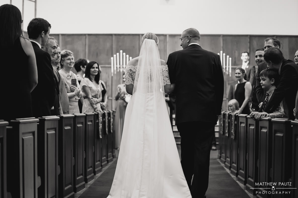 father walking bride down the aisle during wedding ceremony