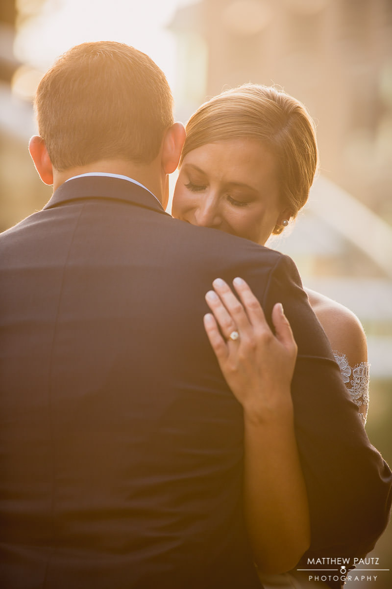 bride and groom hugging at sunset in downtown greenville