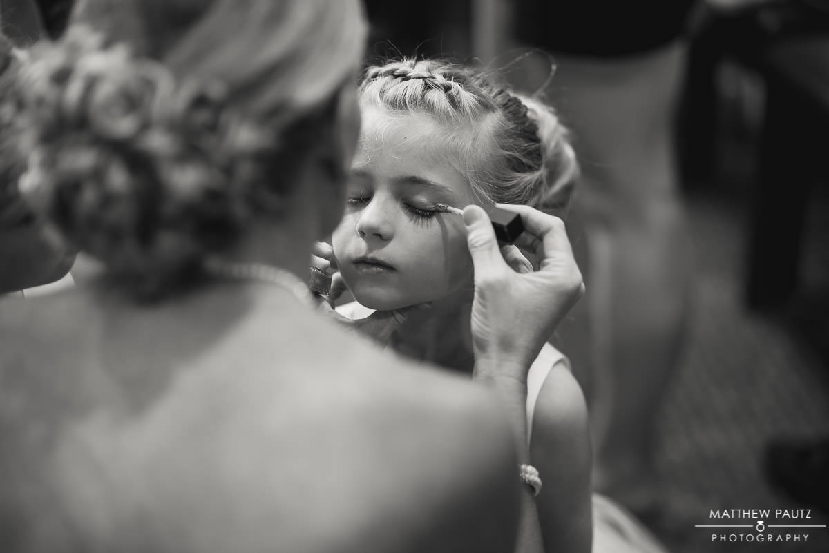 flower girl getting makeup done before wedding ceremony