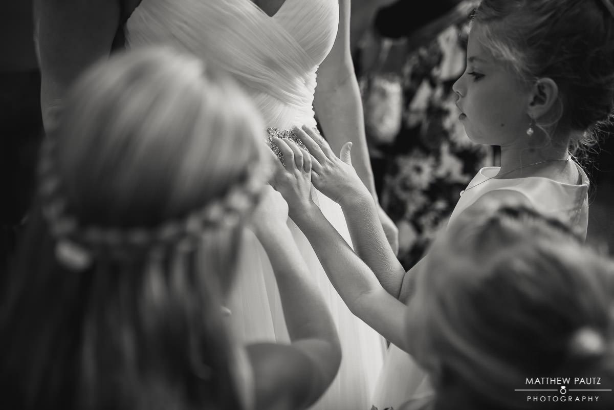 flower girls touching bride's wedding dress before ceremony