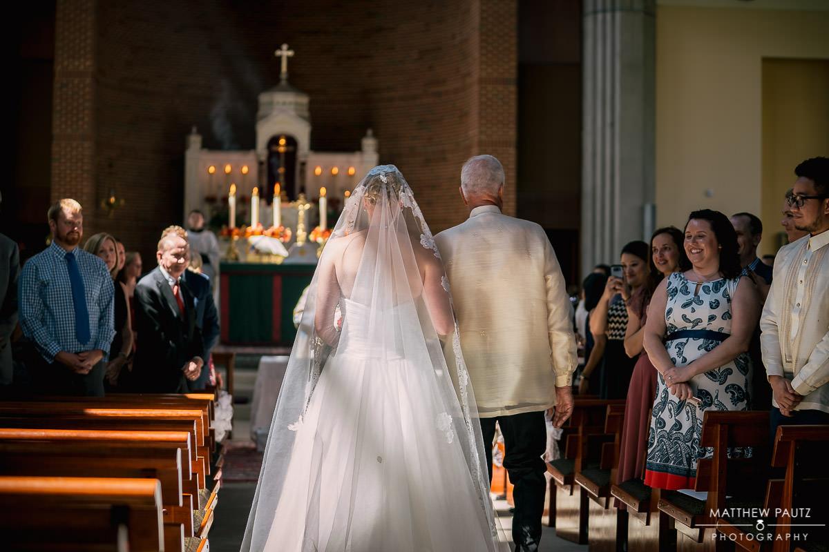 bride walking down the aisle at prince of peace catholic church
