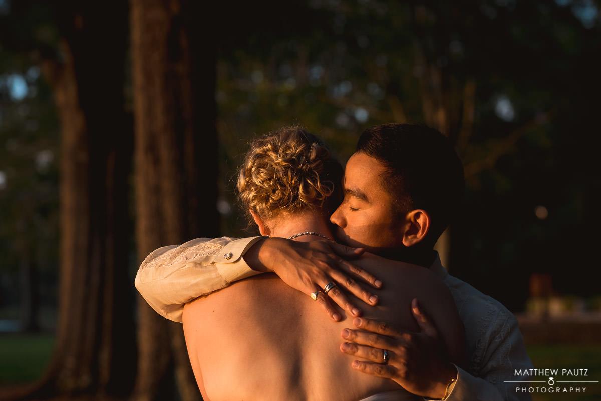 Groom kissing bride on neck during sunset
