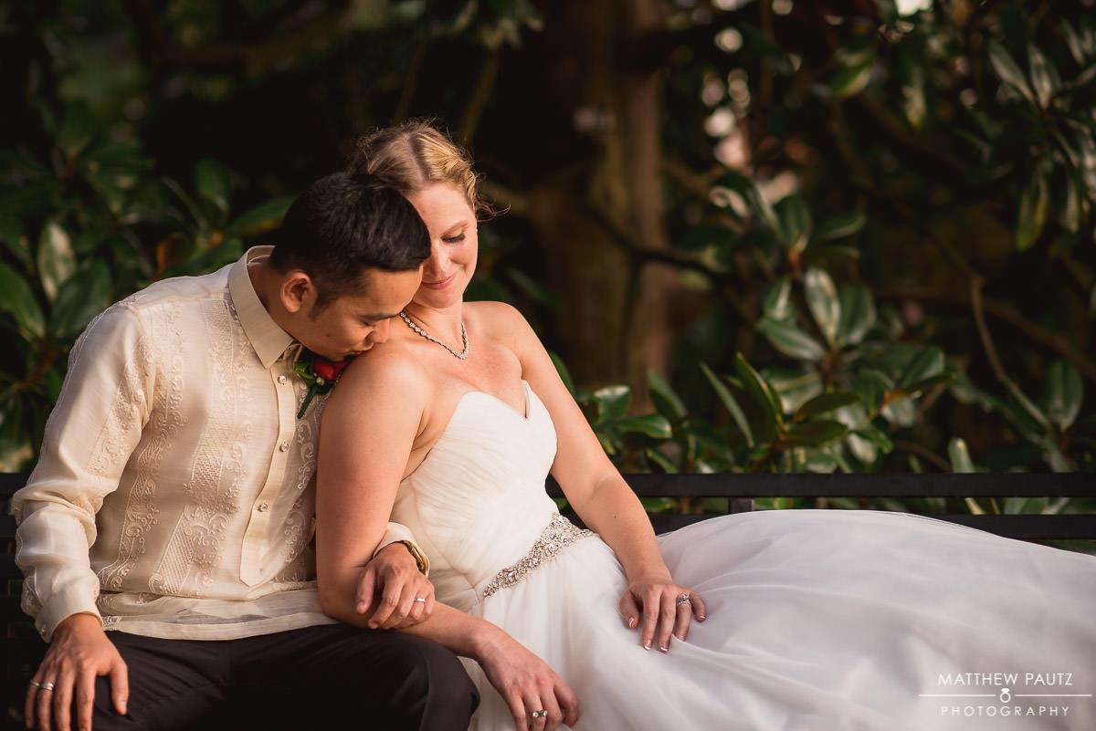 Bride and groom cuddling on park bench at Furman University