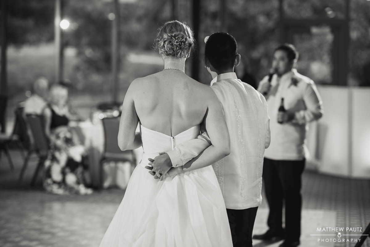 Bride and groom hugging while guests gives wedding toast at reception