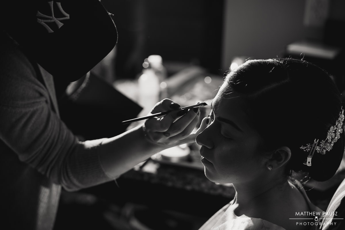 bride having makeup done before getting dressed