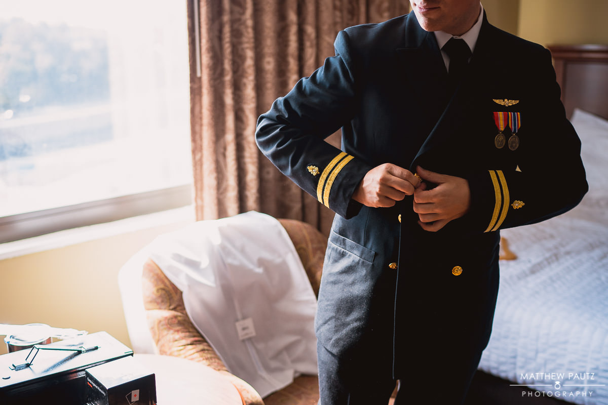 groom putting on military uniform