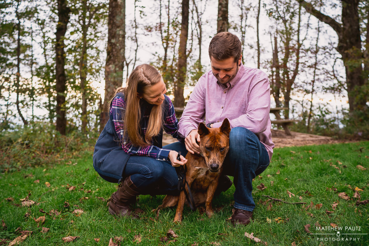 Engaged couple posing with their dog