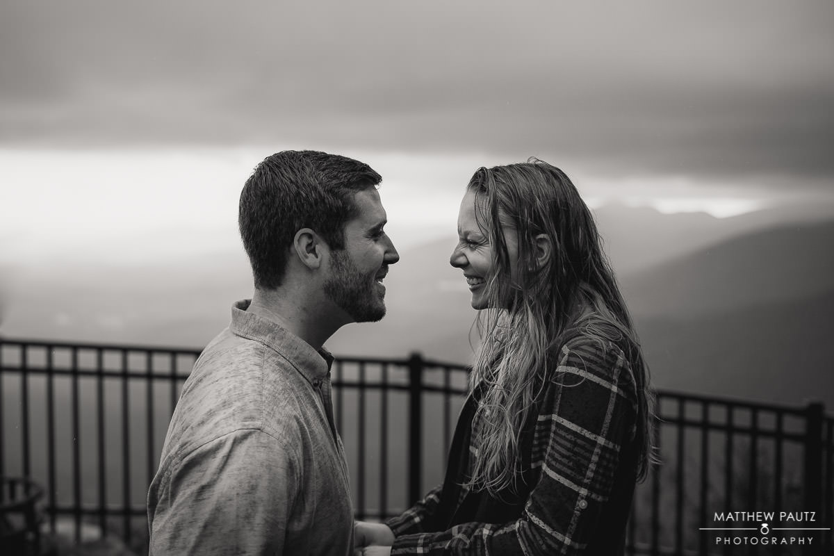 engaged couple laughing in the rain