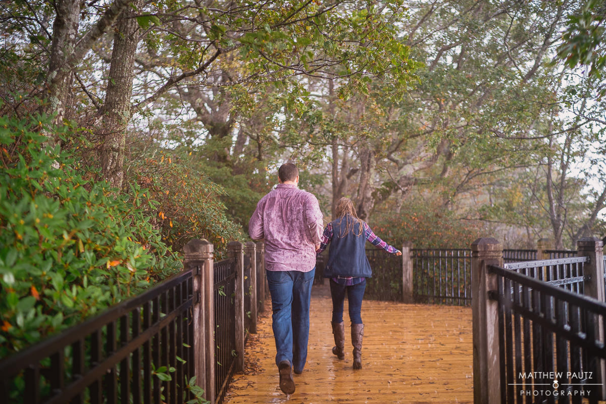 engaged couple running back to car during rain storm