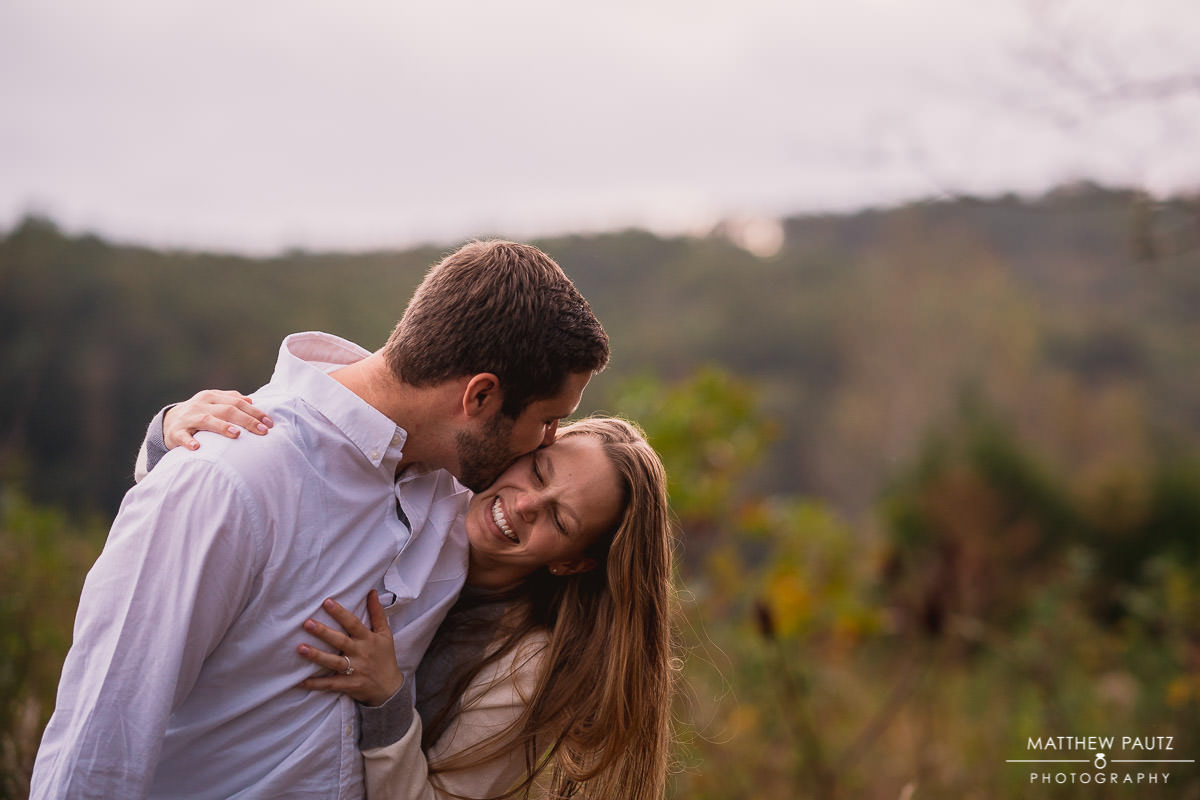 engaged couple kissing and laughing