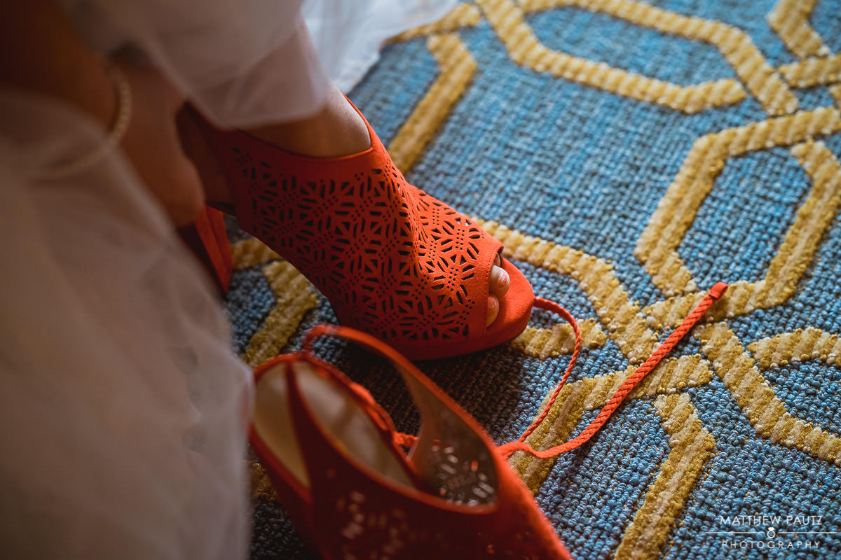 bride putting on red wedding shoes