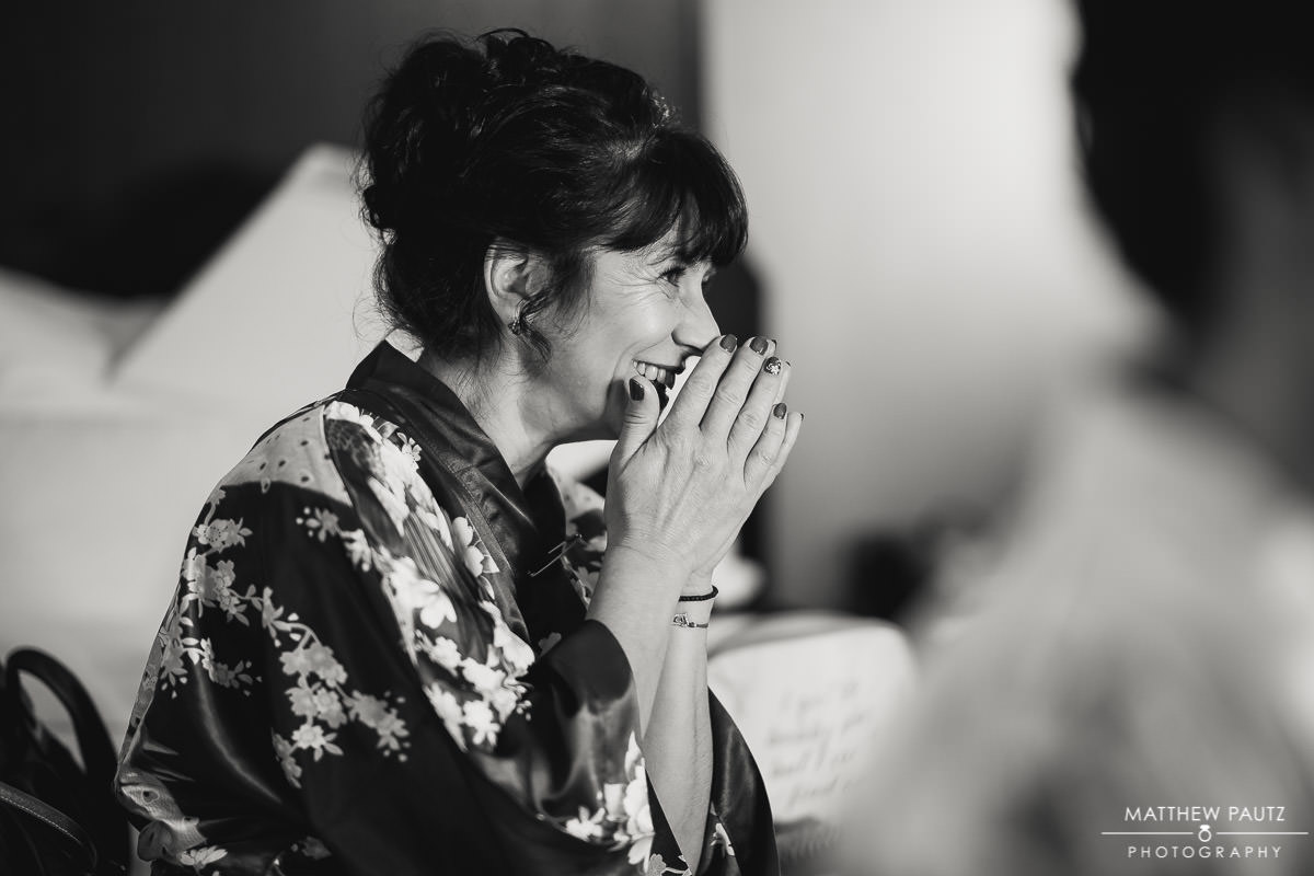 mother of the bride watching bride get ready for wedding