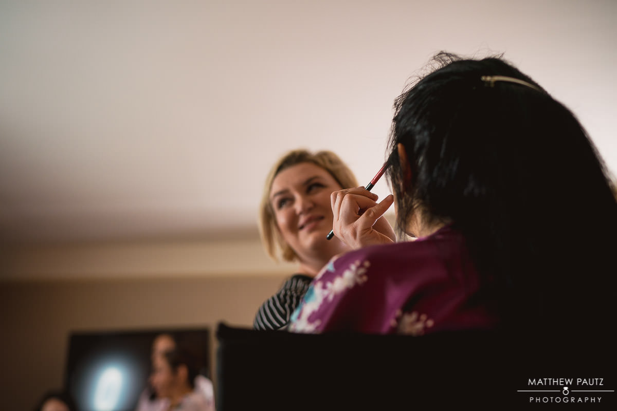 mother of the bride having makeup done before wedding