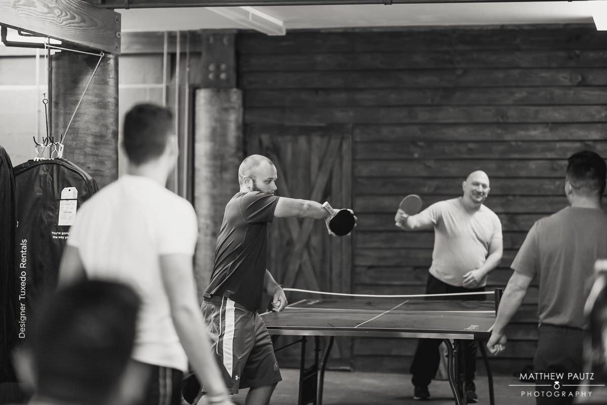groomsmen playing ping pong before getting ready for wedding