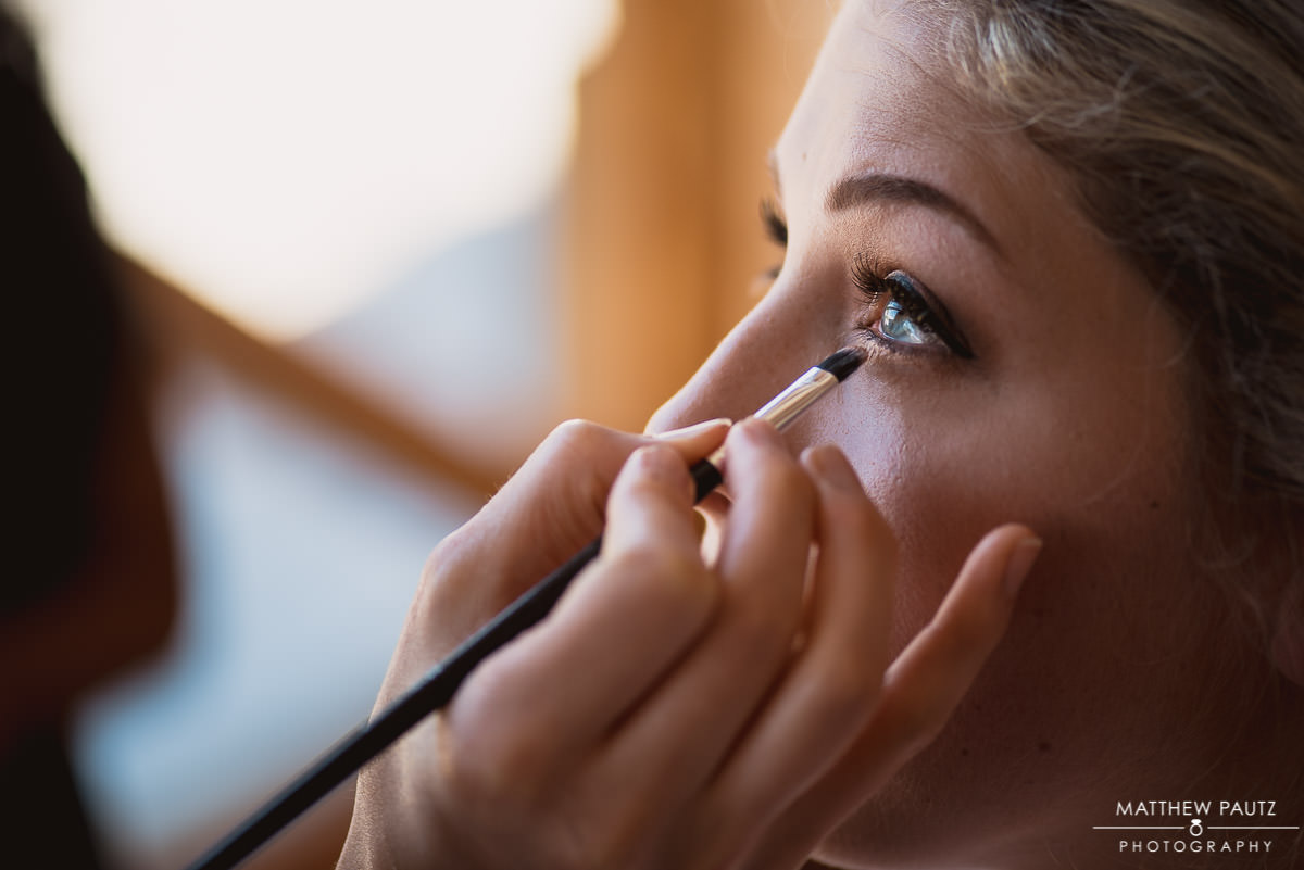closeup photo of bride getting eye makeup done before wedding