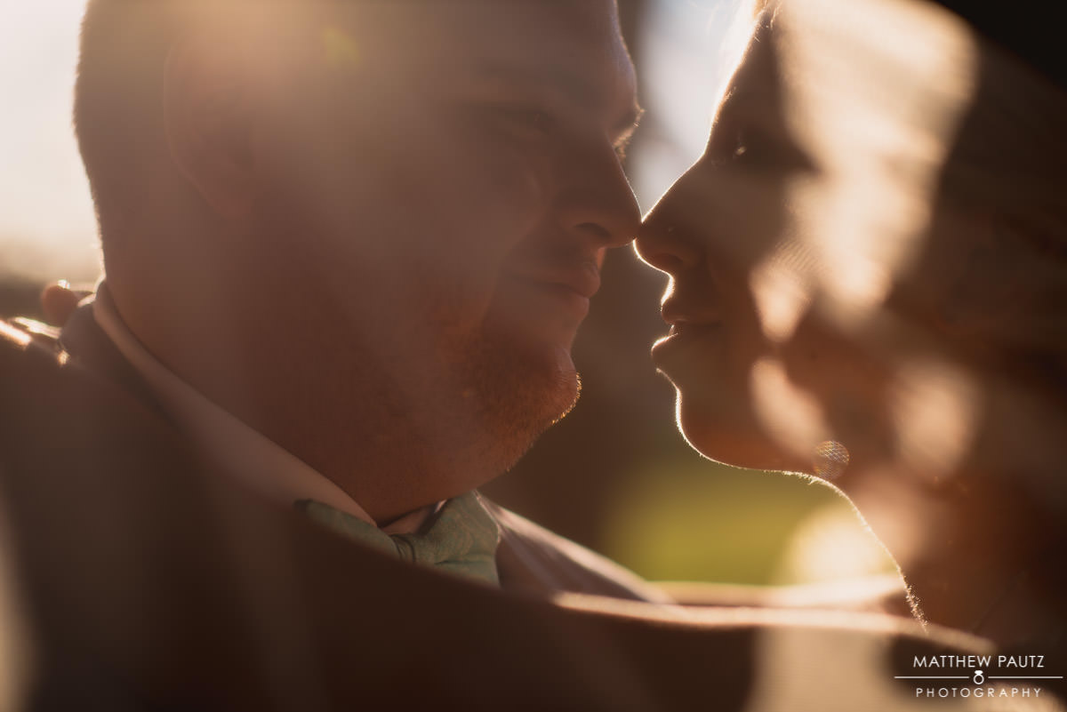 closeup of bride and groom under veil at sunset