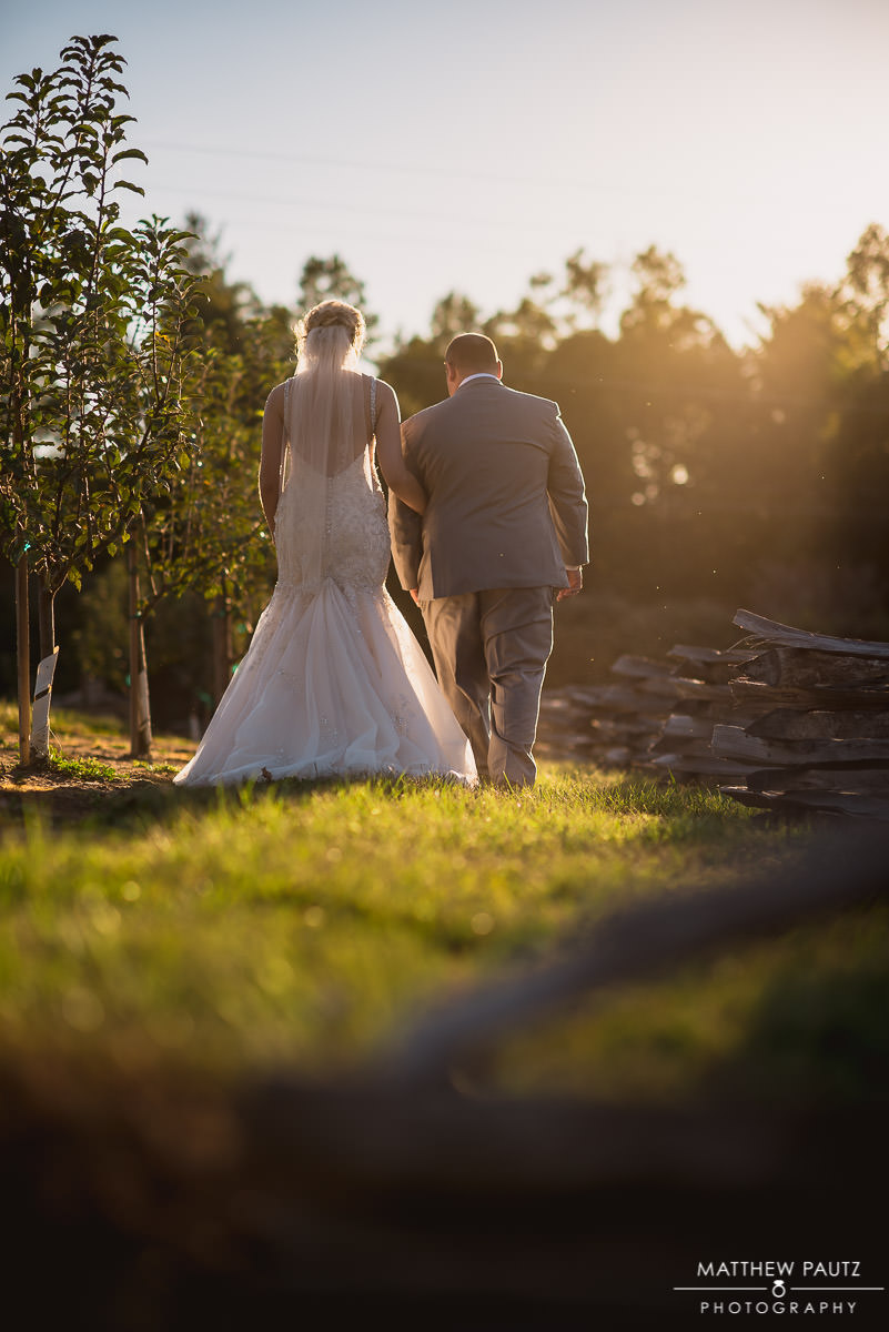 newlywed couple walking along fence at sunset