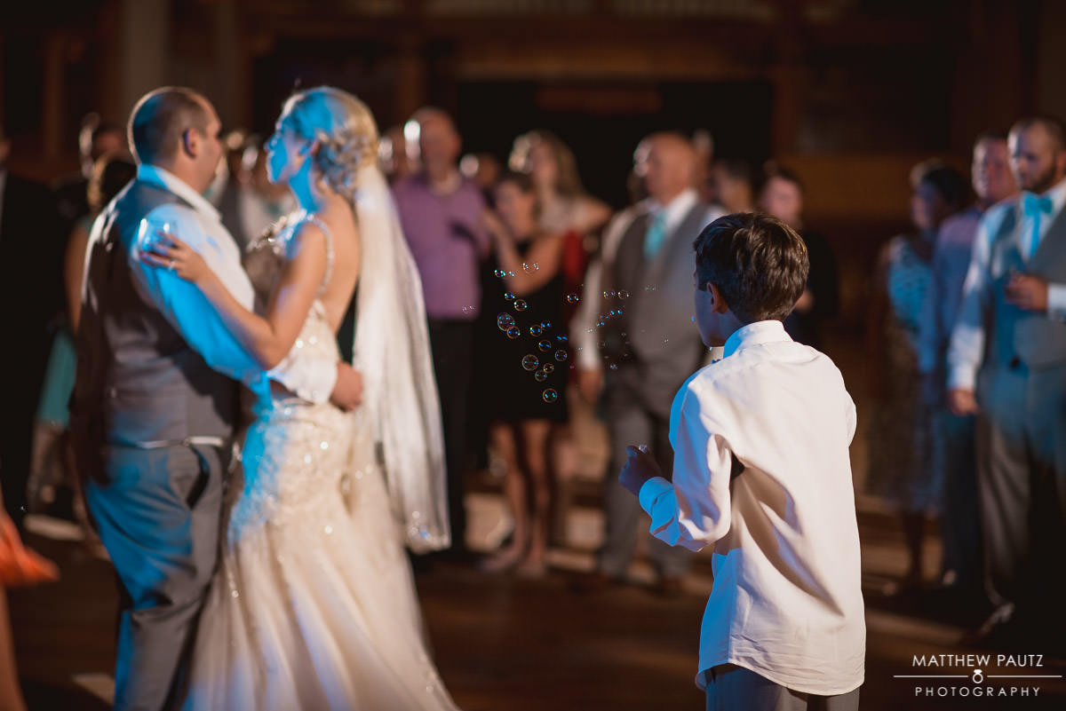 child blowing bubbles while bride and groom dance