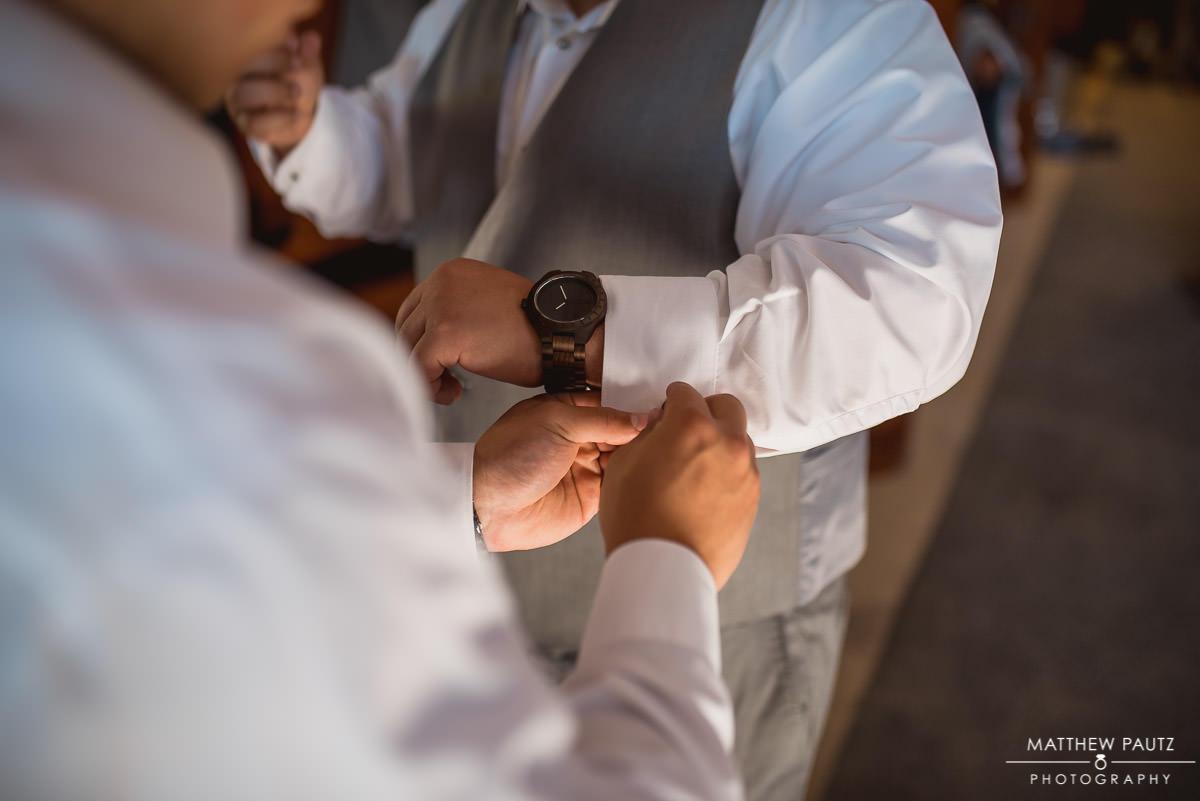 groomsman getting dressed before wedding