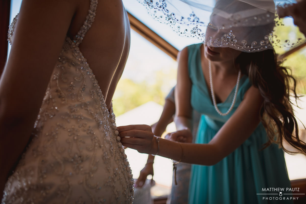 bridesmaid helping bride get dressed before wedding ceremony