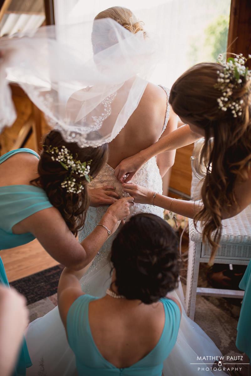 bridesmaids lacing up bride's dress