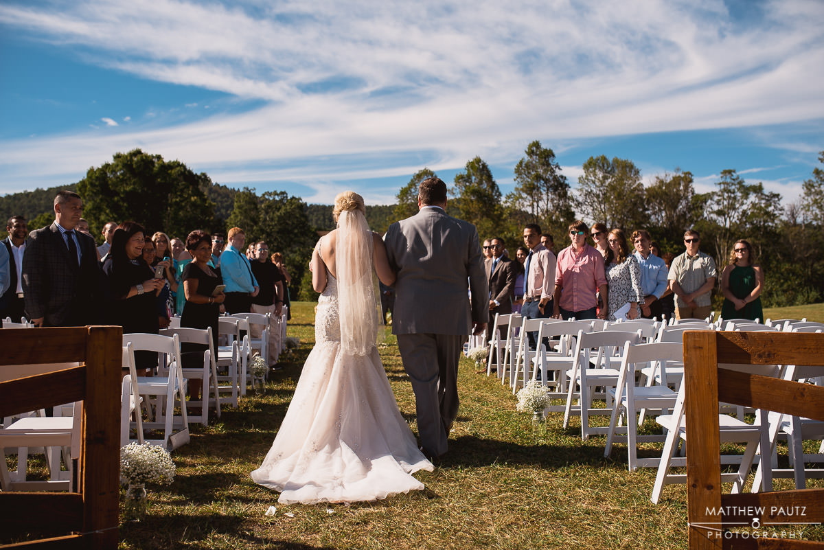 bride walks with father down aisle at outdoor wedding ceremony