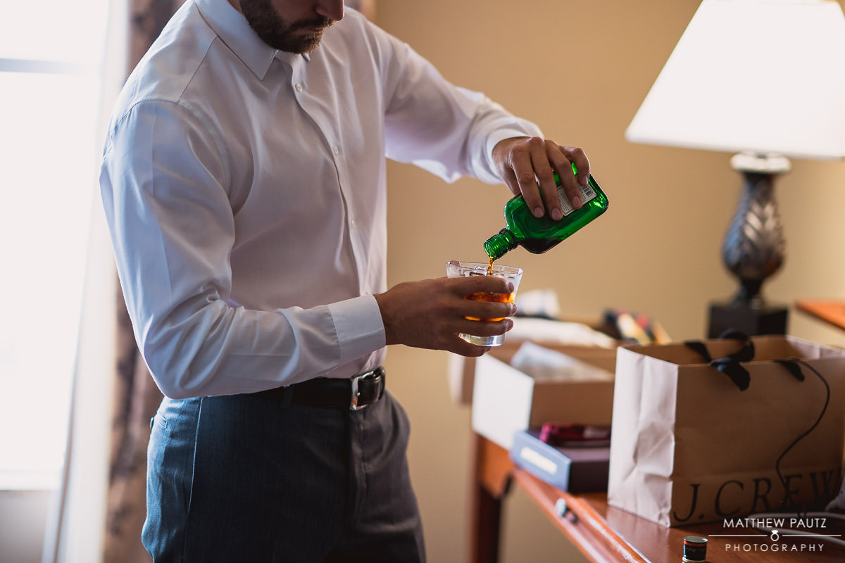 groomsman pouring drinks before wedding