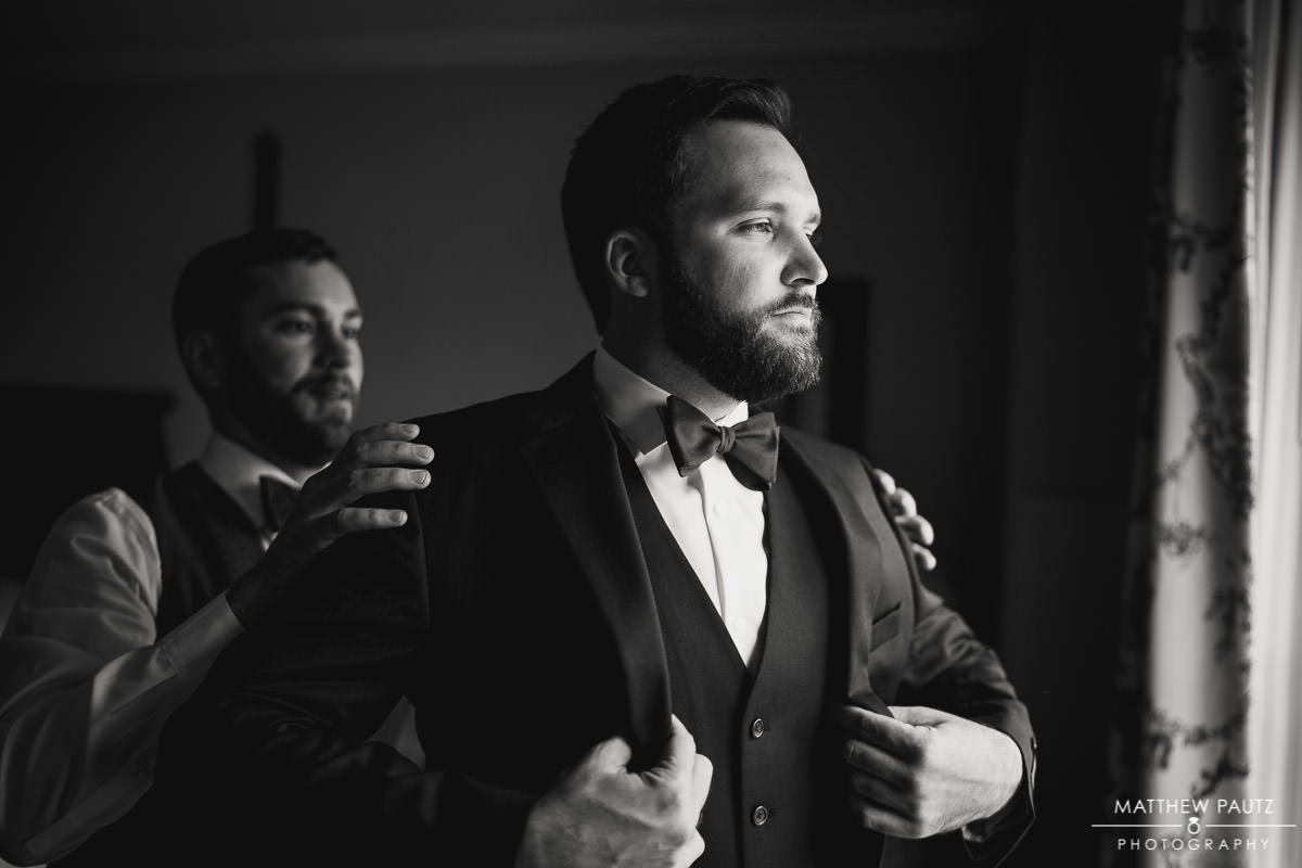 Groom putting on suit before wedding
