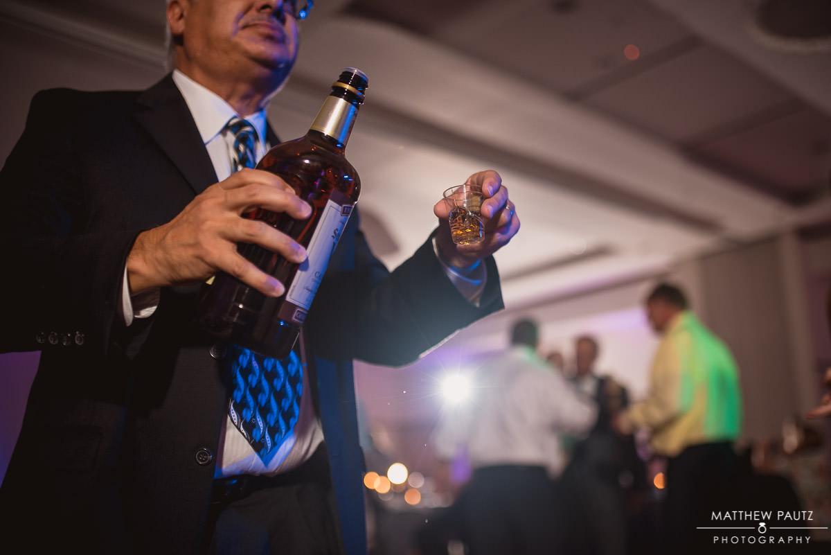 man pouring drinks on dance floor at reception