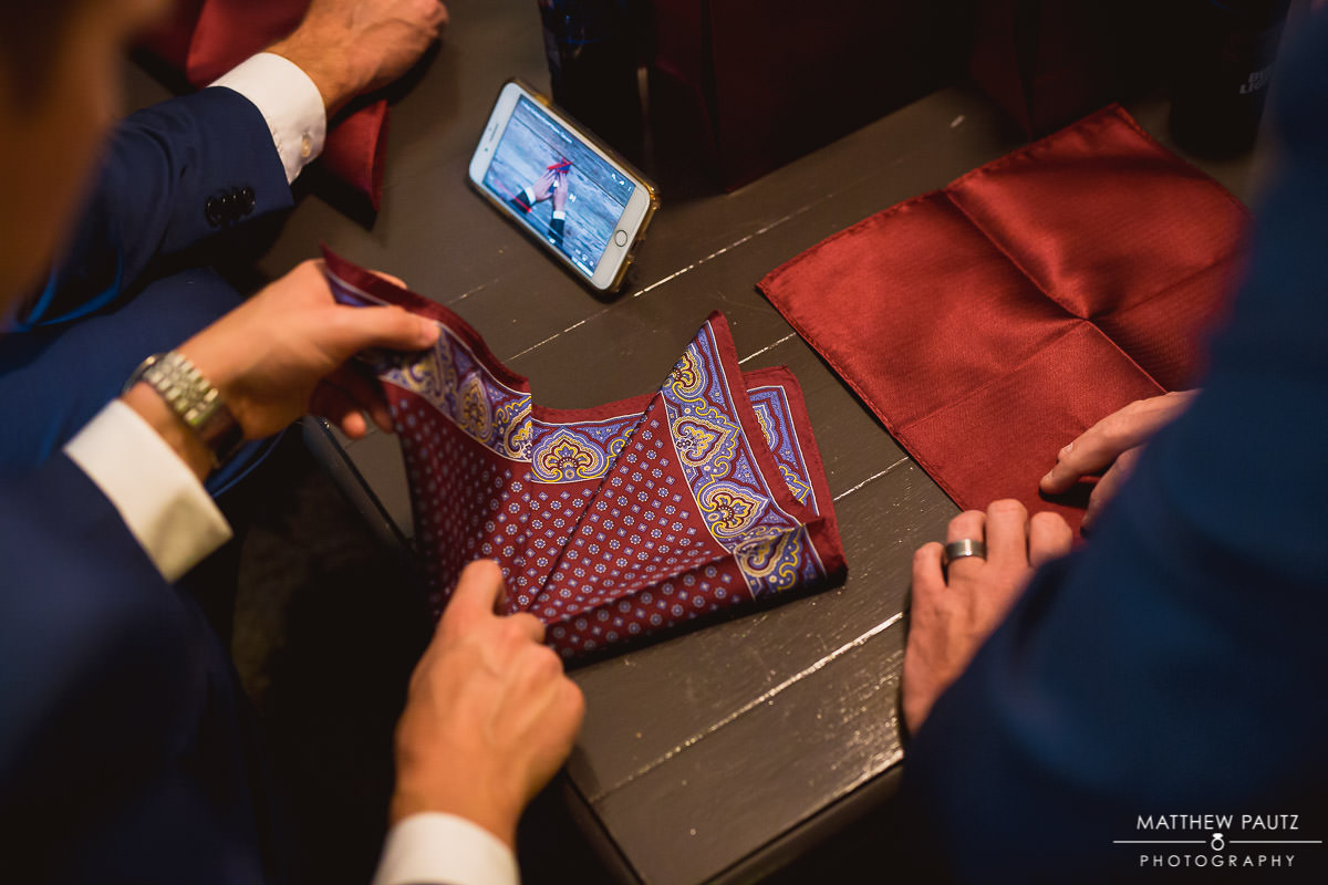 groomsmen learning how to fold pocket square for tux