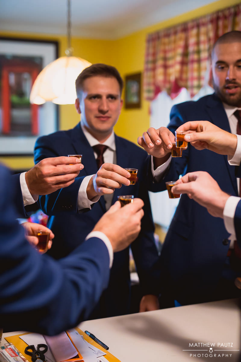 groom having shot with groomsmen before wedding ceremony