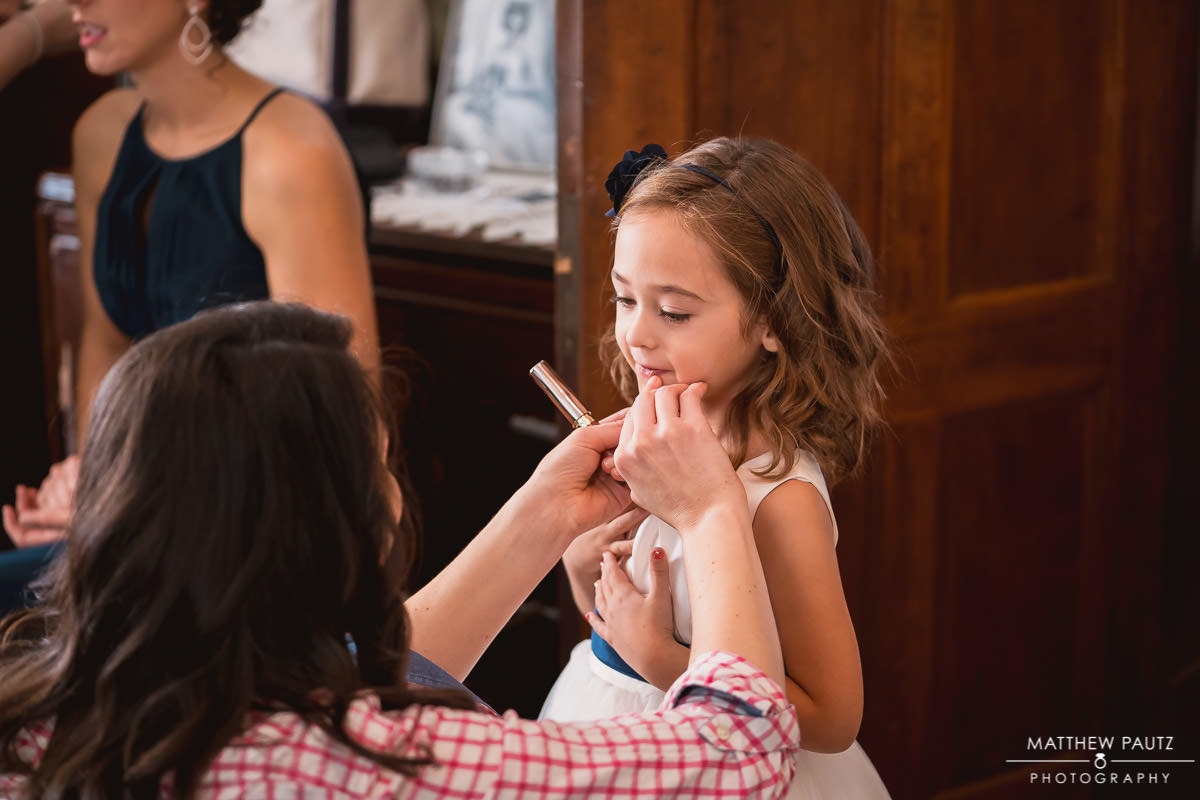 Flower girl having makeup done before wedding